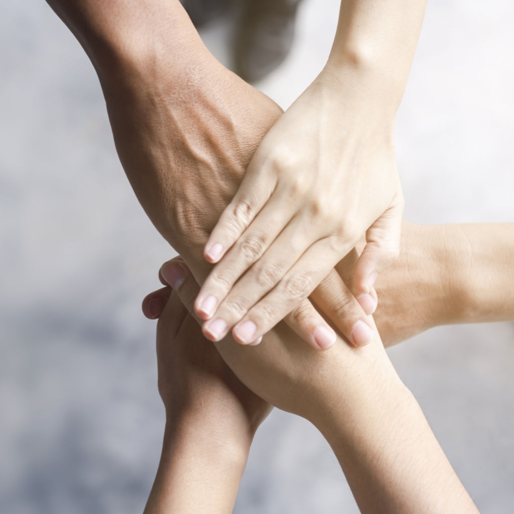 5 hands coming together to display the concept of teamwork