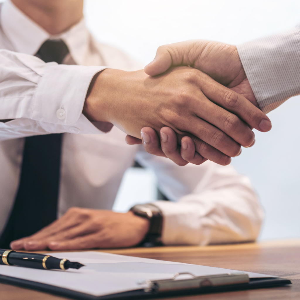 Two businessmen shaking hands with a contract on the table