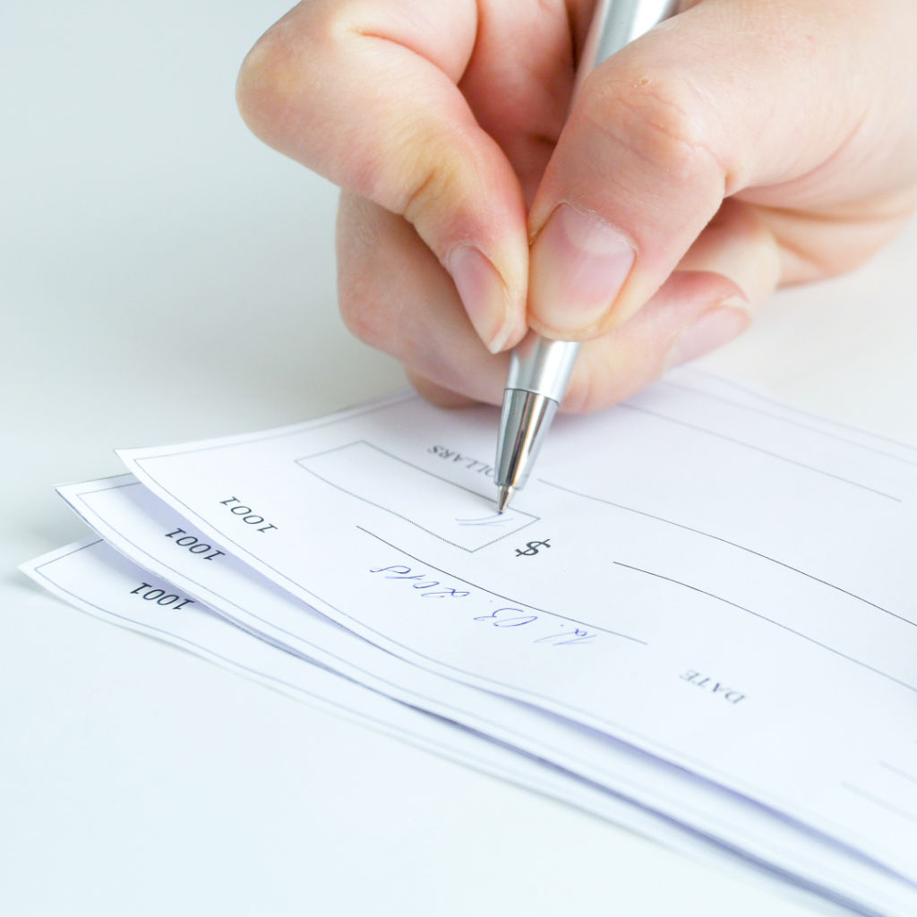 Person filling out and signing payroll checks.