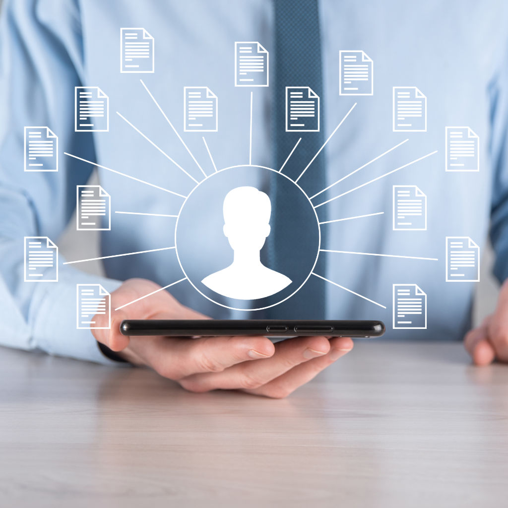 Businessman holding a smart phone with a hovering icon of an employee with many icons of documents extending out. Illustrating the concept of using cloud-based HR & payroll software to manage employee data.